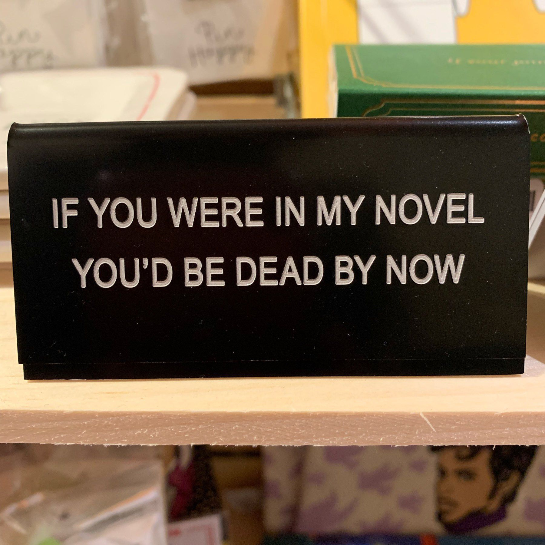 Desk sign reading 'IF YOU WERE IN MY NOVEL YOU'D BE DEAD BY NOW'